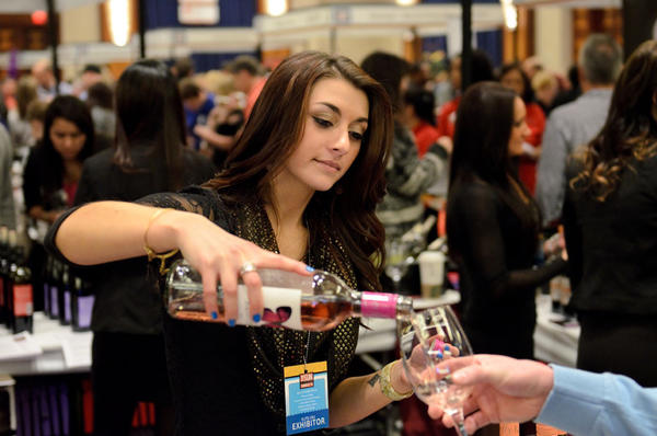 A guest receives a pour of wine from the Diageo Chateau & Estate Wines company.