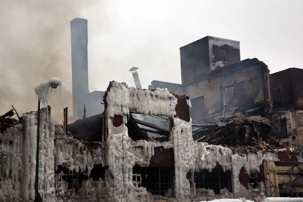 Small flames are rekindled on Sunday as demolition crews knock down the warehouse building at 3757 S. Ashland Ave in Chicago after the building was destroyed by a 5-11 alarm fire.
