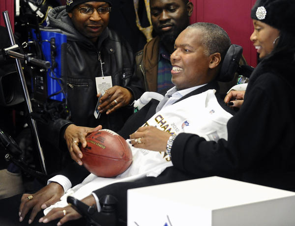 Baltimore Ravens' O.J. Brigance was given a game ball by Ed Reed, not in picture, during celebration with AFC Championship trophy in the locker room. The Ravens defeated the New England Patriots in the AFC Championship game to advance to the Super Bowl.