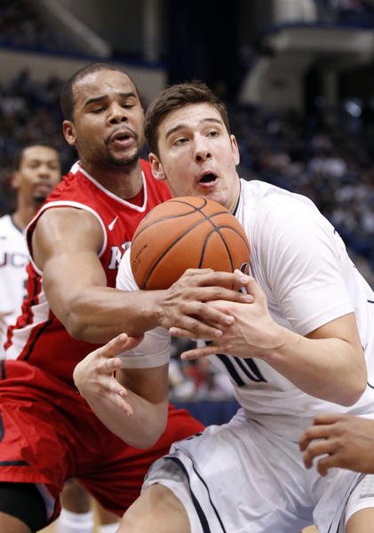 UConn forward Tyler Olander, right, and Rutgers forward Austin Johnson square off during the first half at the XL Center.