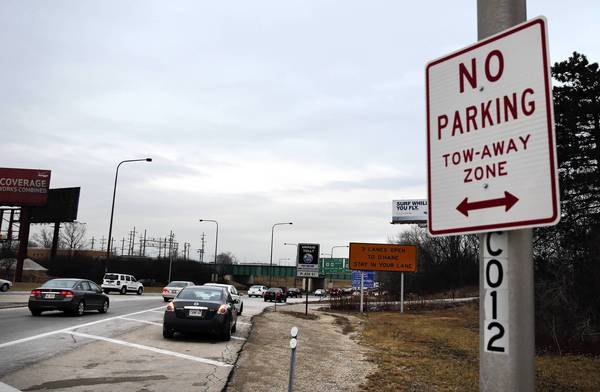 Drivers park on the shoulder of the Interstate 294 ramp to I-190 near O'Hare International Airport last week. Cars sitting on the shoulder on I-190 while motorists await the arrival of passengers at O'Hare is a common sight, though it violates a no-parking zone.