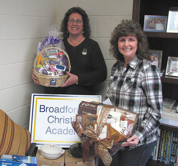 From left, Lisa Haldeman and Denise Burkett display some of the auction items for the Broadfording Christian Academy event planned for Friday, Feb. 15.