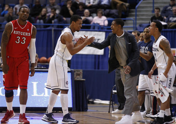 UConn guard Omar Calhoun reacts with coach Kevin Ollie after being fouled by Rutgers forward Wally Judge (33) during the second half at the XL Center.