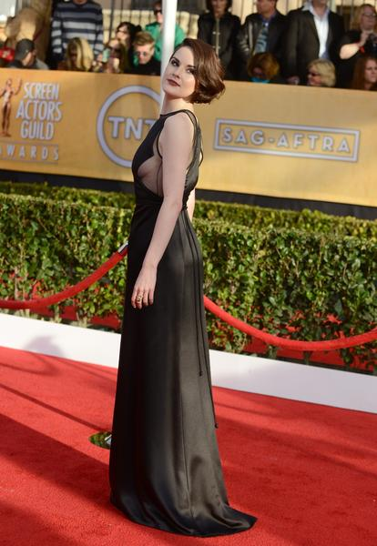 "Michelle Dockery (""Downton Abbey"") looks smoldering in a vintage black Ralph Rucci gown with sheer cutouts revealing the contours of her side cleavage. Yes, side cleavage, and in a good way."