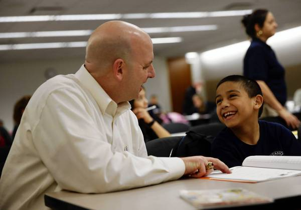 Matthew Bambrick, left, works with Lozano Bilingual & International Center student Ronaldo Gonzalez during a mentoring session this month at Exelon Corp. in Chicago, where Bambrick works.