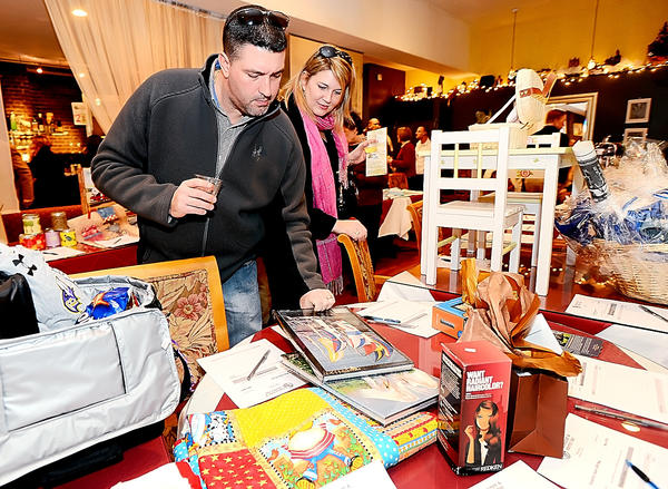 Anthony and Tiffieny Bagley of Hagerstown look over items at the wine and cheese silent auction Sunday at Gourmet Goat in Hagerstown to benefit the Community Free Clinic.
