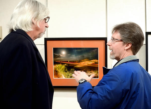 "Photographers Bruce Wilder, left, and Bill Stoler discuss Wilder's photograph ""Highway 12"" Sunday afternoon during the opening reception of the annual Cumberland Valley Photographic Salon at the Washington County Museum of Fine Arts. Wilder's photograph won the Washington County Arts Council, Inc. award for best Photograph by a Washington County, Md., resident."