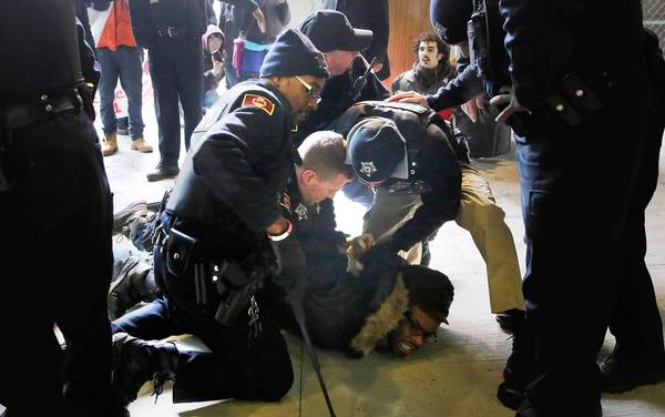 University of Chicago officers handcuff a protester Sunday during a sit-in calling for a trauma center on the South Side.
