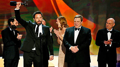 "Surrounded by ""Argo's"" actors, Ben Affleck hoists the statuette that they won for cast performance."