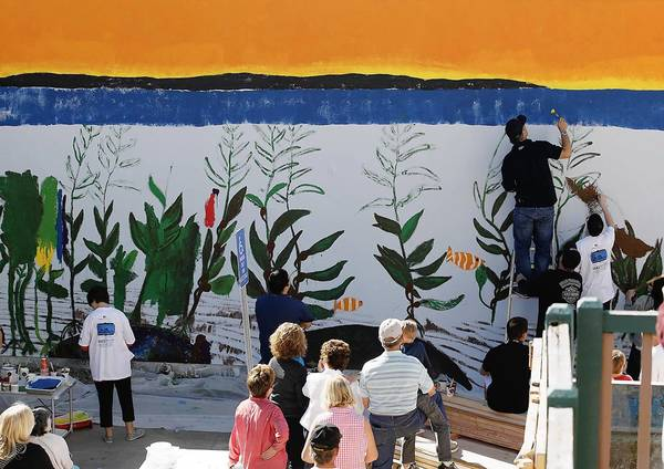 Artist Robert Wyland, on ladder, works on the mural at the Glennwood House of Laguna Beach, a former assisted living facility that will serve about 50 young adults with developmental disabilities.