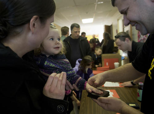 Emma Madison, age 1, held by her mother Michele, of Hellertown, is fingerprinted by Investigator Michael Dattilio as the Hellertown Police give out Child ID packets and fingerprint children as St. Theresa School in Hellertown kicks off Catholic Schools Week on Sunday.