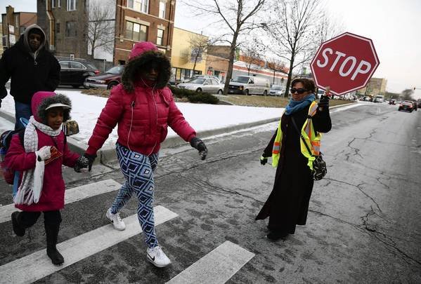 On the Far North Side, crosswalk monitor Elisa Salinas halts traffic to allow pedestrians to cross at Clark Street and Thome Avenue near Hayt Elementary School in Chicago's Edgewater neighborhood.