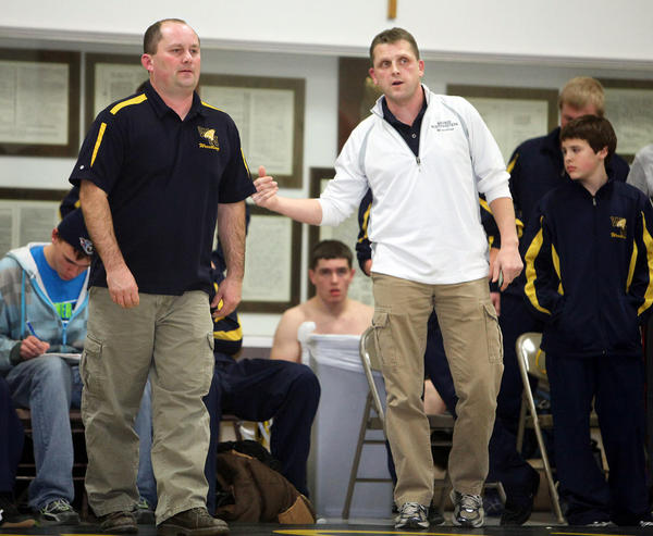 Warner-Northwestern wrestling coaches Rob Fortin, left, and Jeff Larson, right, talk on the sideline during a dual against Sioux Falls O'Gorman last Friday night. The men have worked together to form a cooperative wrestling program that is making its mark.