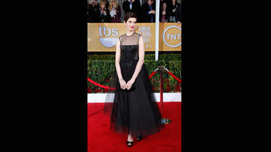 Anne Hathaway's Giambattista Valli gown has a fairy-tale look, with a sleeveless bodice of embroidered sheer tulle and a full sheer skirt revealing a shorter skirt underneath.