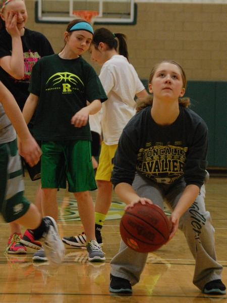 Jori Ewart, left, watches as Callie Steinbach, right, crouches down to shoot a free throw before the competition began at the Knights of Columbus free-throw contest at Presentation Colleges Strode Activities Center on Sunday.