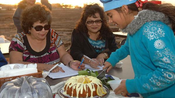 "Juanita Ortiz (right), 10, cuts pieces of her citrus baked goods contest entry, a lemon cake, for judges Margaret Navarro (left) and Gloria Rivas during the first Citrus Festival in Calipatria on Sunday. Ortiz said, ""My grandmother baked the cake and I decorated the cake with frosting and squeezed lemon."""