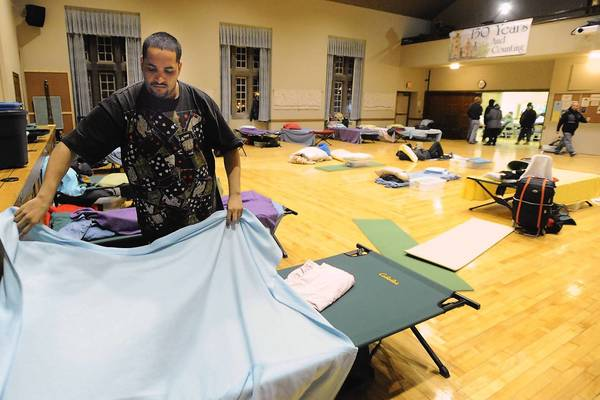 Hector Gonzalez gets a cot ready at the Cathedral Church of the Nativity in Bethlehem Thursday. Homeless for about three months, he takes shelter on cold nights at area churches.