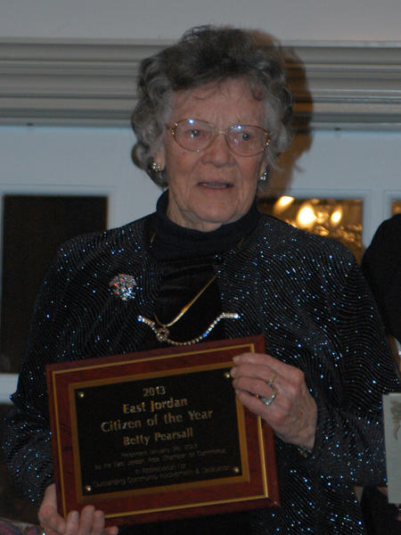 East Jordan citizen of the year Betty Pearsall accepts a plaque for her contributions to the community Saturday during the East Jordan Chamber of Commerce annual meeting at Castle Farms.
