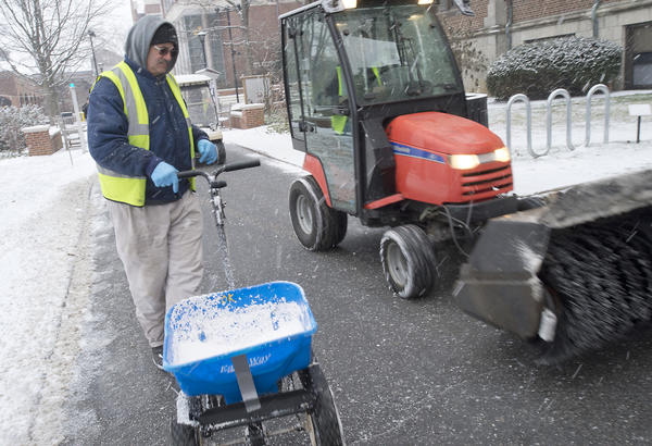 Muhlenberg College groundskeeper Bill Ruhe uses a spreader to apply calcium to the walk way as a light snow begins to coat surfaces in Allentown on Monday around 9 am.