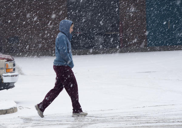 A Muhlenberg College student marches through a flurry of snow flakes on the campus as a light snow begins to coat surfaces in Allentown on Monday around 9 am.