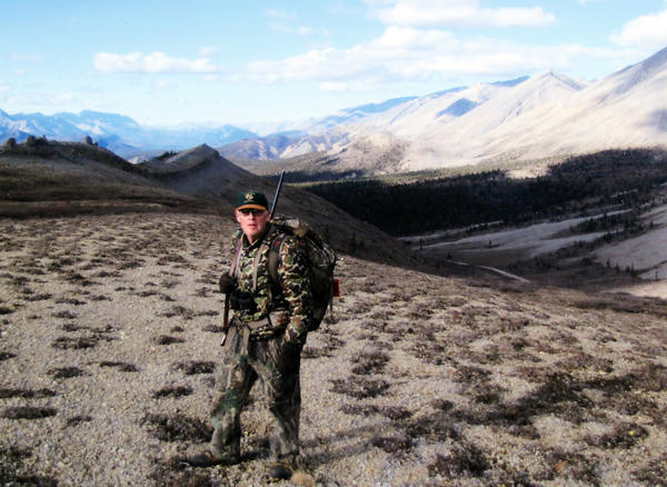 With mountains looming in the background, Roger Rozema of Charlevoix is ready to hunt during a recent caribou hunting excursion to Canada's Northwest Territories.