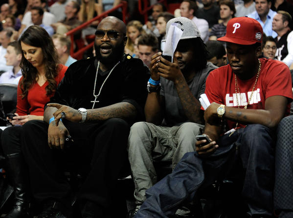 Recording artist Rick Ross cheers for the Miami Heat as everybody around him checks out their phones during the second half of the Heat's game against the Milwaukee Bucks, Tuesday night, January 4, 2011, at AmericanAirlines Arena.