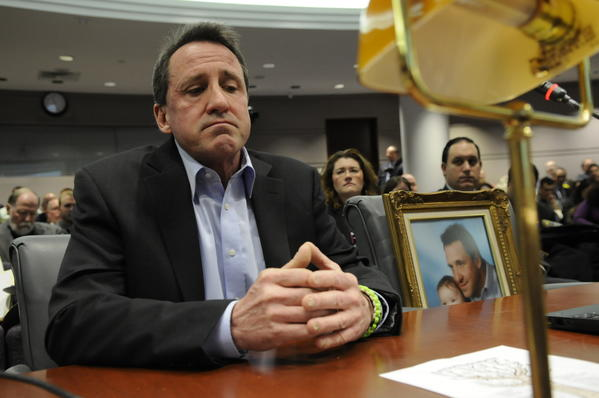 "Neil Heslin, father of Jesse Lewis who was one of twenty children killed in the Sandy Hook School massacre, pauses for a moment as he speaks against the need for high-capacity magazines for weapons at a public safety hearing on gun control at the Legislative Office Building. ""Jesse was my buddy, he was my best friend,"" he said. He brought a framed photo of him and Jesse that sits on the chair next to him."