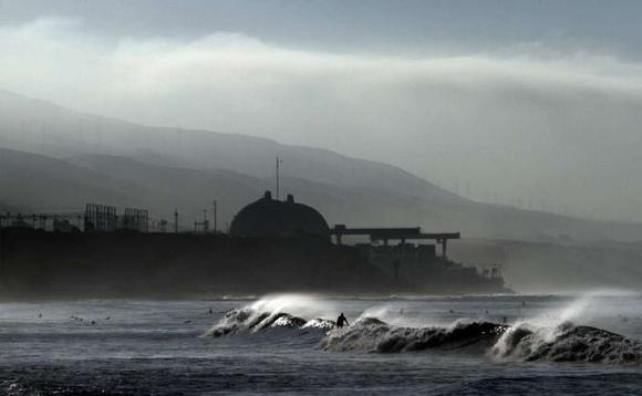Surfers work the waves at Lower Trestles near San Clemente while the darkened San Onofre nuclear plant rises up in the background.