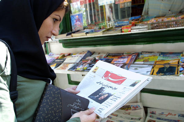 In this file photo from October 2003, an Iranian woman looks at the front page of the reformist daily Shargh in the center of Tehran.