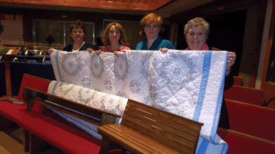 Mary Margaret Werner, Brandy Merkel, Mary Boehnke and Donna Paul pose behind a cross-stitched quilt to be auctioned off at the 3rd annual Fellowship Banquet and Auction at 6 p.m. Feb. 16, at the Berlin Community Building. The quilt is one of many items up for sale at the event that has raised more than $5,400 for mission work through the Berlin Brethren Church.
