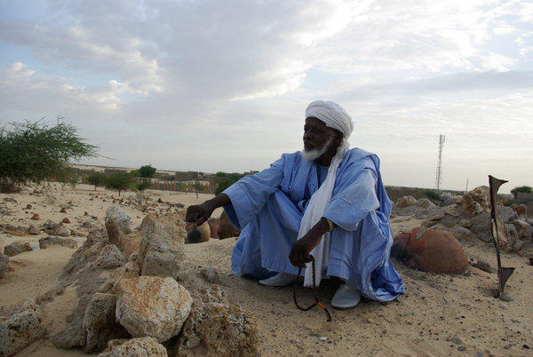 A man in Timbuktu, Mali, prays beside the remains of tombs of locally venerated Islamic saints, whose mausoleums were destroyed.