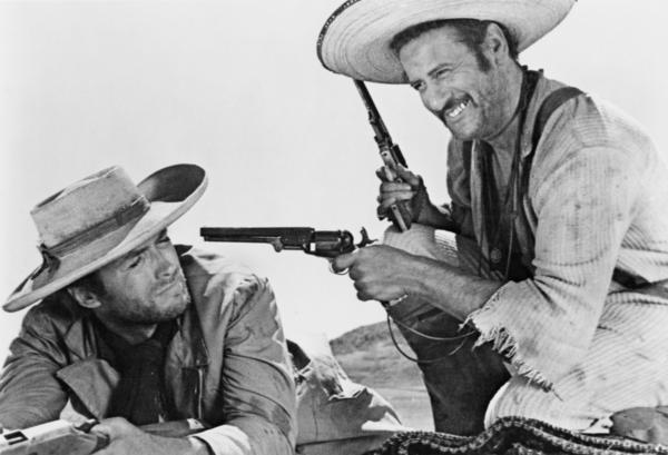 "Tuco (Eli Wallach, right) trains what IMFDB identifies as a Colt 1851 Navy on the man with no name (Clint Eastwood), who Tuco calls ""Blondie."""