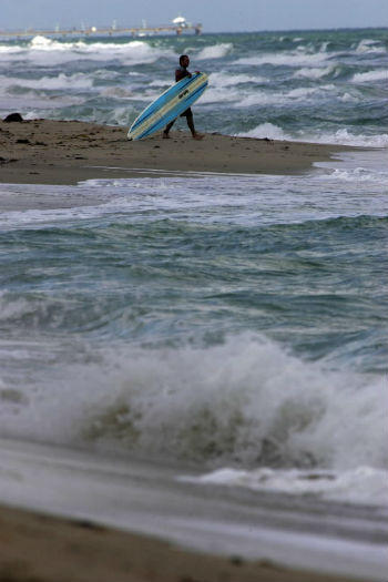 A surfer gets ready to challenge the rough waters off Fort Lauderdale beach.