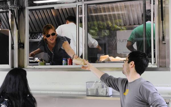 Highland Park is considering whether to allow on its streets food trucks similar to the one pictured in this 2011 Tribune file photo, which shows Heather Behm, center, serving Jeff Henderson,right, from the Hummingbird Kitchen Evanston's primary food truck in Evanston.
