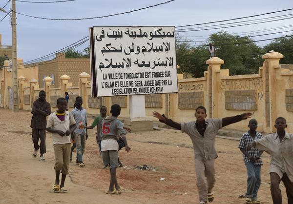"Children wave after Malian and French soldiers entered the historic city of Timbuktu. A sign attesting to its occupation by Islamist militants reads, ""The city of Timbuktu is founded on Islam and will be judged only by the Islamic law."""