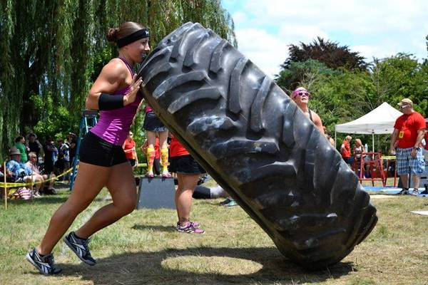 Emily Beers, 26, lifts a tire in the RX'd division in a Test Your Metal Competition at Cedar Beach during Sportfest in Summer 2012. She placed 3rd.