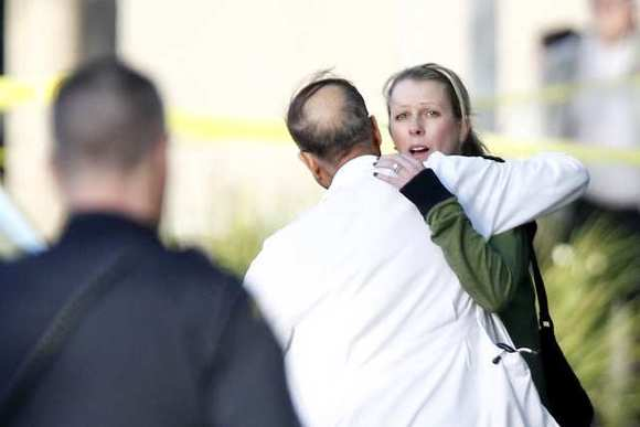 Two people embrace outside the medical office building on Superior Avenue where a doctor was shot and killed Monday afternoon.