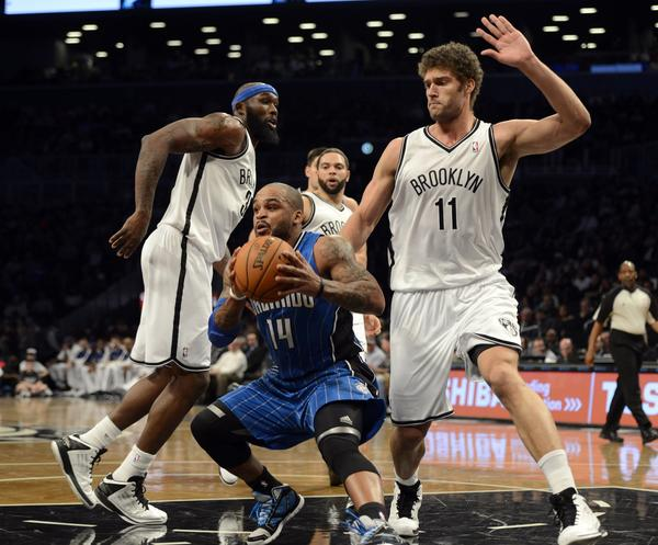 Orlando Magic's Jameer Nelson (C) drives against Brooklyn Nets Brook Lopez (R) during their NBA game at the Barclays Center on January 28 , 2013 in the Brooklyn borough of New York City.