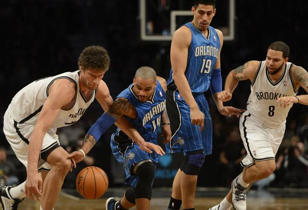 Orlando Magic's Jameer Nelson (2nd-R) and Brooklyn Nets Brook Lopez (L) vie for the ball during their NBA game at the Barclays Center.