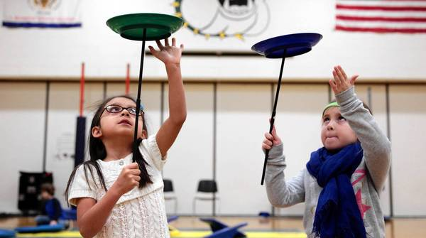 Kindergartners Zyanya Alvarez, left, and Addison Kozlowicz spin plates in PE at Libertyville's Butterfield School. The full-day program, which is new this school year, costs families $3,500.