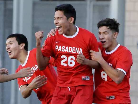 Pasadena's Danny Banuelos (26) celebrates with his teammates after scoring a second half goal for the Bulldogs.