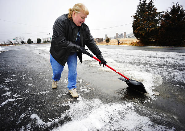Patty Morris scoops slush Monday in front of her Country Crossroads Deli on Hollow Road near Hancock. Overnight weather iced the area and closed schools in Hancock.