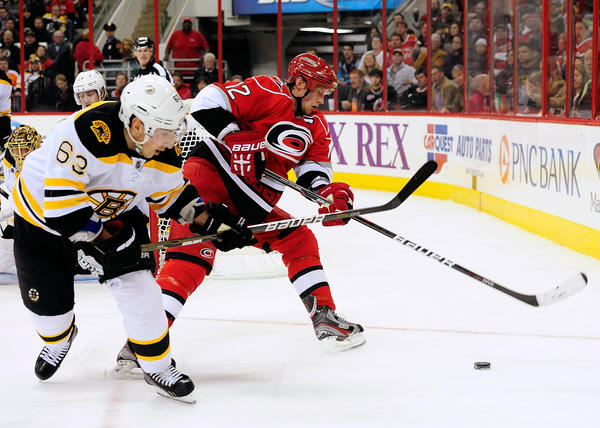 Brad Marchand #63 of the Boston Bruins and Eric Staal #12 of the Carolina Hurricanes chase a loose puck behind the net during play at PNC Arena.