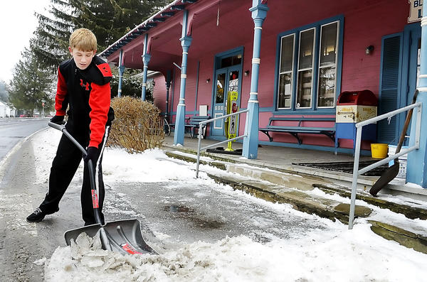 Jake Atkinson, 14, clears ice Monday in front of the Blue Ridge Summit (Pa.) Free Library in Franklin County. Jake, who said he frequently visits the library, volunteers his time to clear the steps and sidewalk of the library when there is snow and ice.