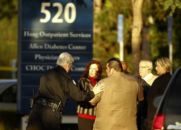 Police help stunned employees move to safety at an office building near Hoag Hospital in Newport Beach after a gunmen shot and killed a doctor. A suspect is in custody.