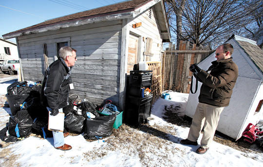 Aberdeen Planning and Zoning code enforcement officer Robert Baumgartner, right, takes photographs of trash and debris as he and fellow officer Mike Olson inspect a property in Aberdeen.