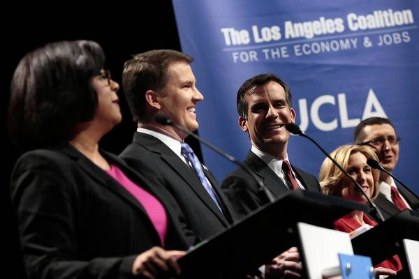Los Angeles mayoral candidates, from left, Jan Perry, Kevin James, Eric Garcetti, Wendy Greuel and Emanuel Pleitez enjoy a light moment before Monday's debate at UCLA's Royce Hall.