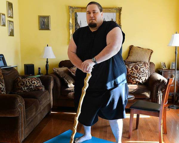 Ben Miller of Nazareth poses on a yoga mat in his home. At over 400 pounds he is teaming up with retired pro wrestler Diamond Dallas Page to try to lose more than 200 pounds.