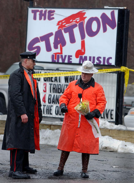 A West Warwick policeman and a Rhode Island State Trooper guard the entrance to the nightclub.  All that is left of the club is the sign on Route 3.  The trooper is holding a bouquet of flowers given to him by a passing motorist to be placed near the rubble of the club as a tribute.