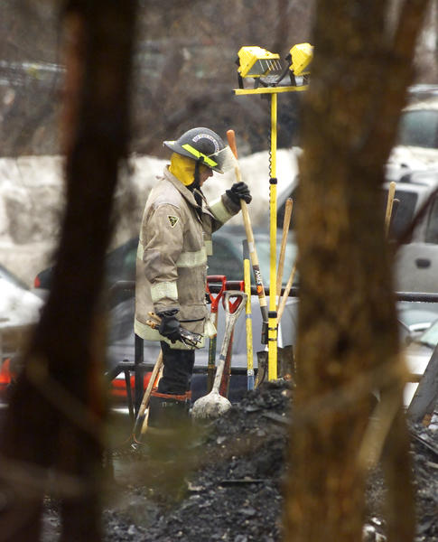 A Rhode Island state fire marshal chooses a tool to use in raking the debris from the West Warwick nightclub fire as the investigation of the fire continues.